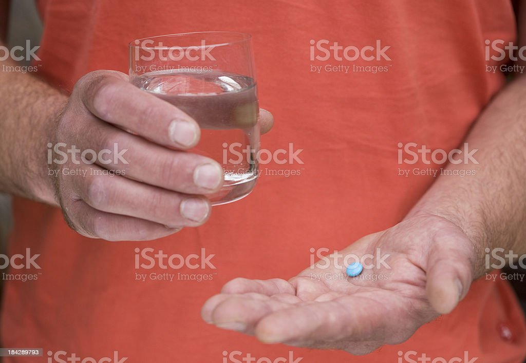 Taking blue tablets royalty-free stock photo