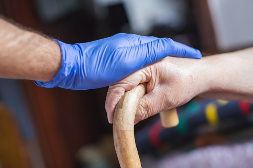 gloved hand on elderly person's hand holding a walking stick