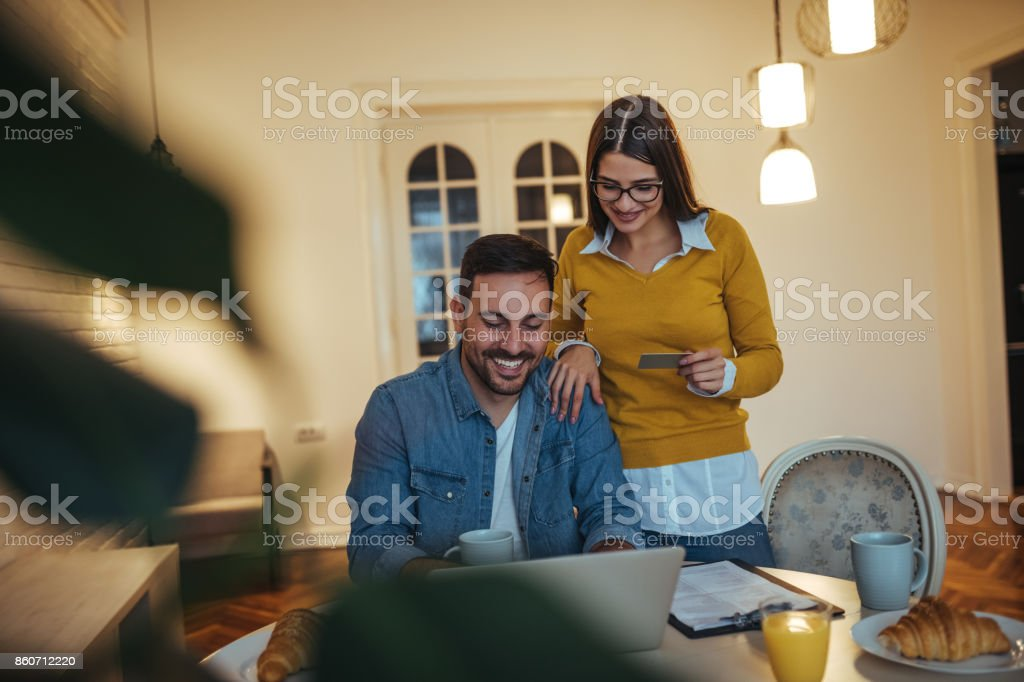 Couple paying bills online at home.