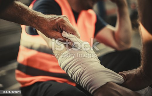 Close up of unrecognizable manual worker assisting his colleague with physical injury in a warehouse.