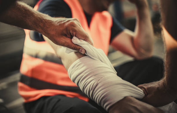 Taking care of physical injury at work! Close up of unrecognizable manual worker assisting his colleague with physical injury in a warehouse. misfortune stock pictures, royalty-free photos & images