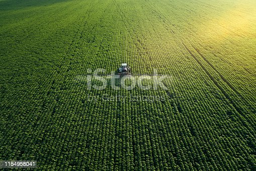 istock Taking care of the Crop. Aerial view of a Tractor fertilizing a cultivated agricultural field. 1154958041