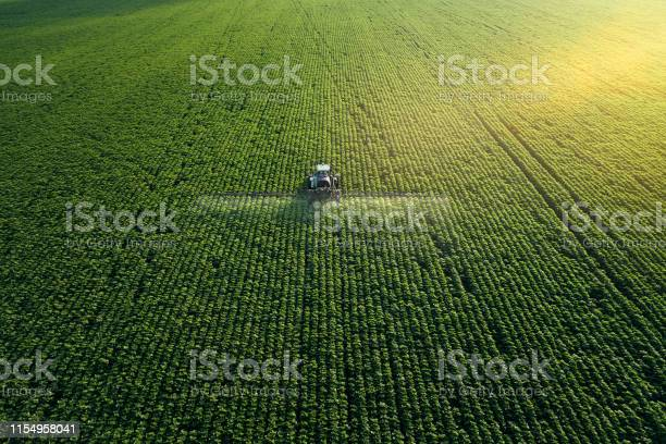Photo of Taking care of the Crop. Aerial view of a Tractor fertilizing a cultivated agricultural field.