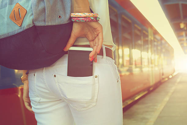taking cellphone from/to the pocket on railway station. - pocket stock photos and pictures
