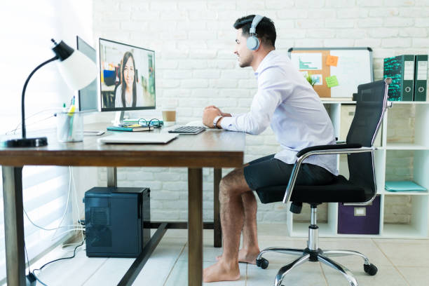 Taking conference call comfortably at home Young businessman taking a conference call barefoot and while wearing shorts comfortably at home shorts stock pictures, royalty-free photos & images