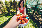 Man's hand is taking an Easter egg from a basket held by young woman.