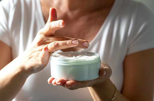 Female hands holding a jar of facial cream and taking a little bit with her finger for application