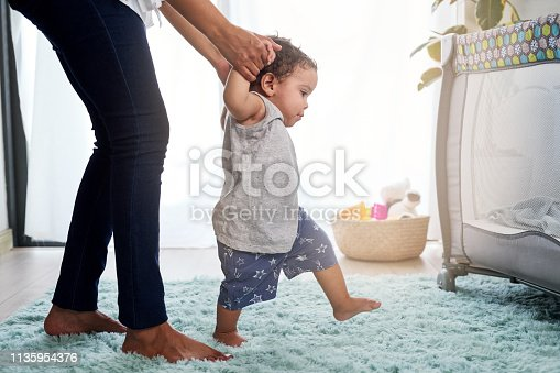 Baby's first steps holding mother's hands, cute unstable walking in home nursery with cot