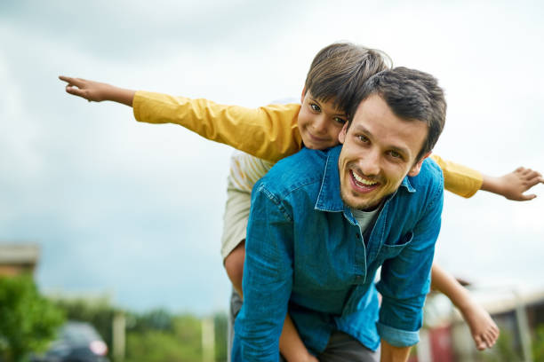 Taking flight with my little man Portrait of a cheerful young father giving his son a piggyback ride outdoors father stock pictures, royalty-free photos & images