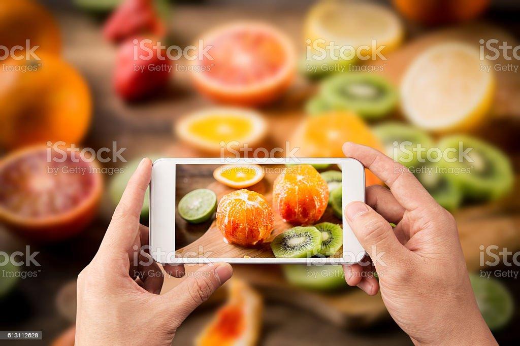 Taking fruit photo with smart phone stock photo