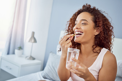 Shot of an attractive young woman taking her medication in her bedroom at home