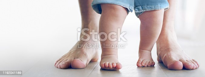 Cropped shot of an unrecognizable little baby girl learning to walk with her father behind her at home