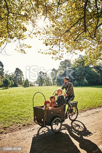 Full length shot of a young man taking his family around the park on a cargo bike