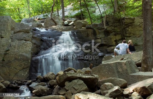 A young couple resting beside a beautiful waterfall