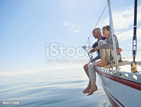 Shot of a loving mature couple on a sailboat looking out onto the ocean