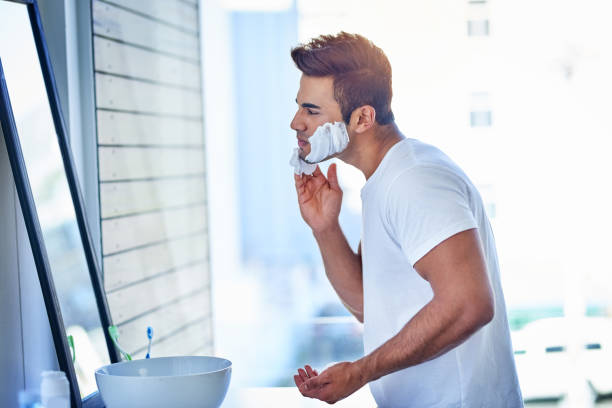 Taking it all off Shot of a handsome young man shaving his facial hair in the bathroom facial hair stock pictures, royalty-free photos & images