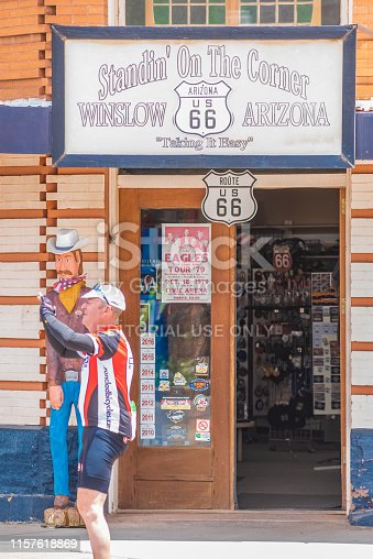 Cyclist taking a photograph of his friends while standing on the corner in Winslow Arizona.