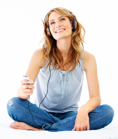 Young woman listening to music while wearing a pair of headphones