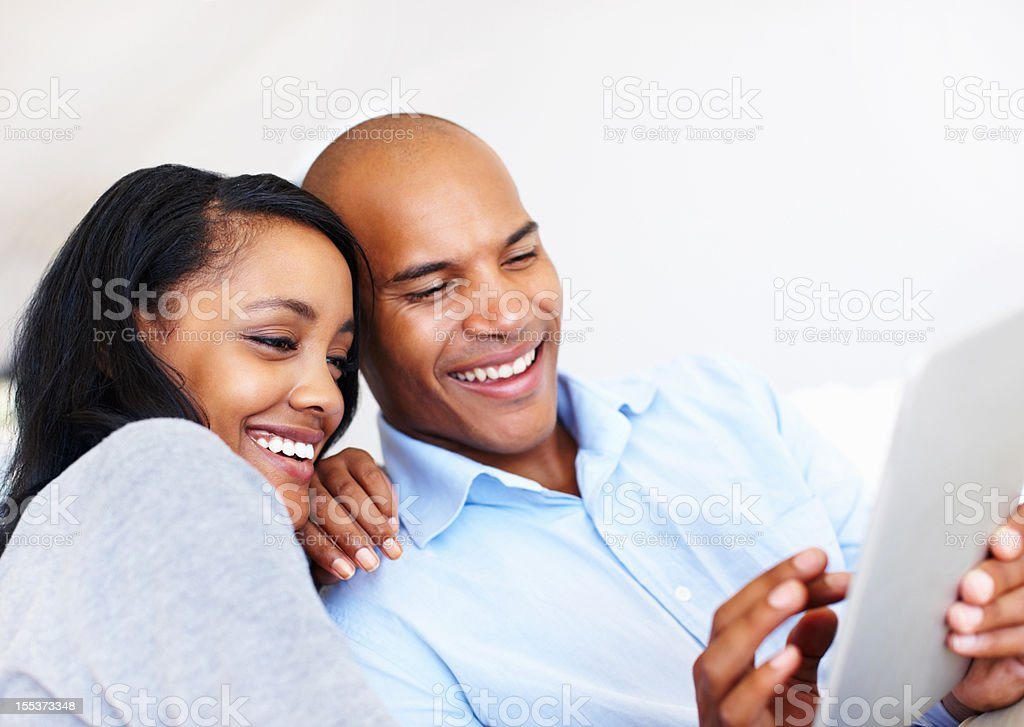 Taking it easy with their useful tablet royalty-free stock photo