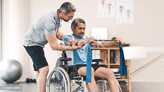 Shot of a senior man in a wheelchair exercising with a resistance band along side his physiotherapist