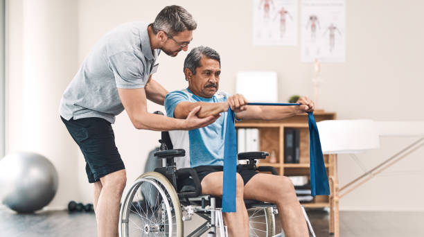 Taking it up a notch day by day Shot of a senior man in a wheelchair exercising with a resistance band along side his physiotherapist paralysis stock pictures, royalty-free photos & images
