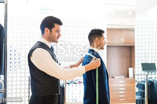 istock Taking Measurements For Formal Suit At Rental Shop 1134289062