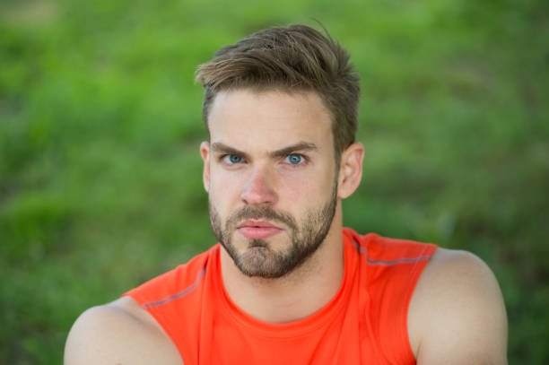Taking minute break. Runner relaxing in shadow. Man with bristle strict face, grass background. Man unshaven looks handsome and cool. Guy bearded and attractive relaxing at meadow during workout stock photo