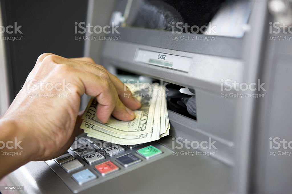 Taking money from ATM machine stock photo