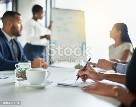 Cropped shot of an unrecognizable woman making notes while sitting in a meeting
