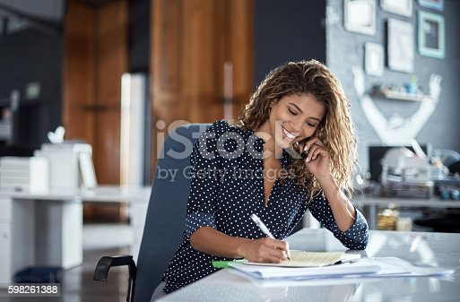 istock Taking notes of her business call 598261388