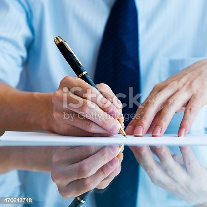 Close-up of businessman's hand writing something.