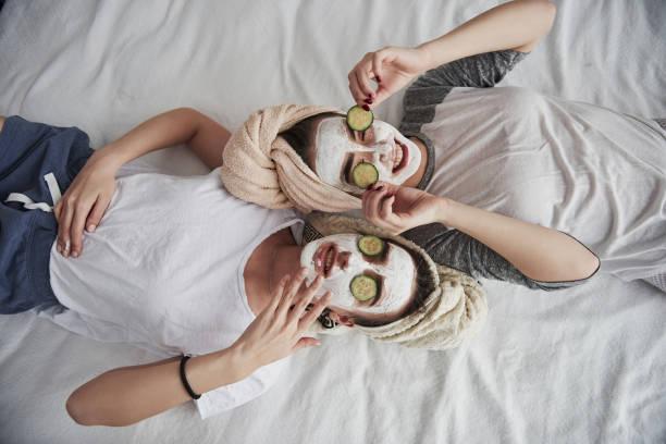 Diese Dinge abnehmen. Auf dem weißen Bett liegen. Top View. Konzeption der Hautpflege mit weißer Maske und Gurken im Gesicht – Foto
