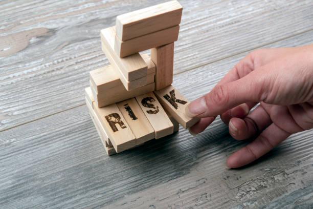 木製のブロックタワーから1ブロックを取る - リスクマネジメント ストックフォトと画像