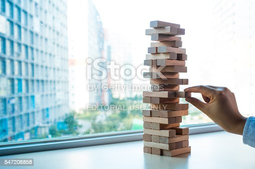 Beijing, China- July 10, 2016: Jenga is a game of physical and mental skill created by Leslie Scott. Taking one block from wooden blocks tower that stability decrease