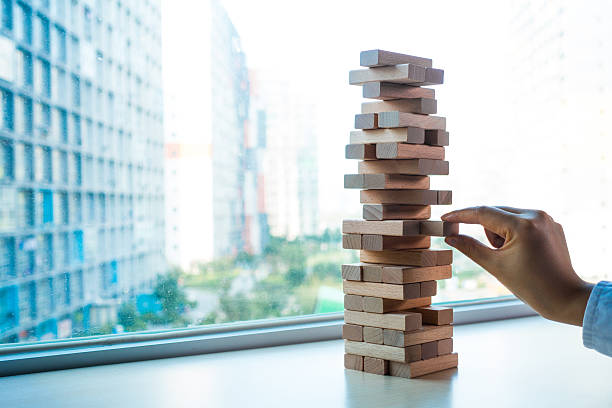 taking one block from wooden blocks tower - torre struttura edile foto e immagini stock