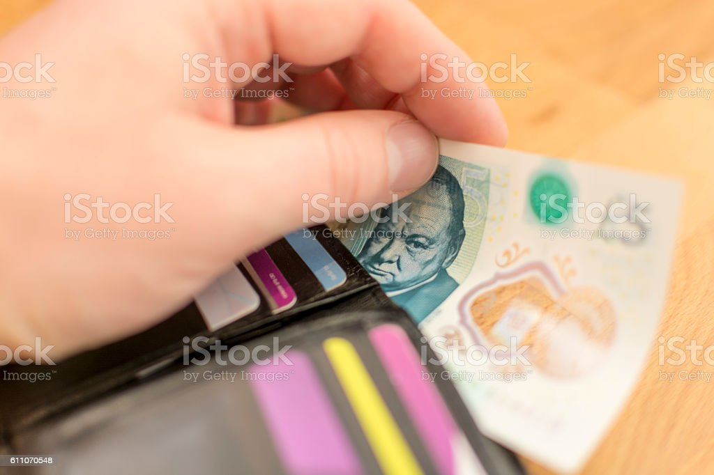 Taking out a 2016 UK Five Pound Note in Wallet stock photo