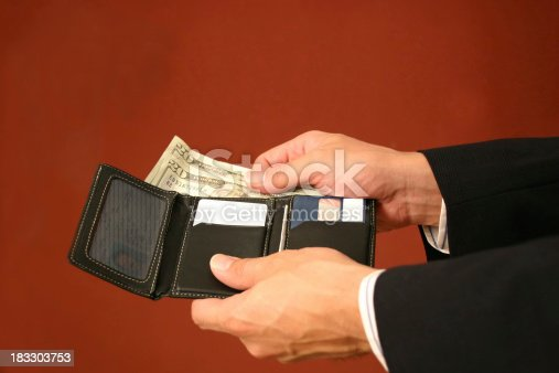 Close-up of businessman taking out some twenty dollar bills.