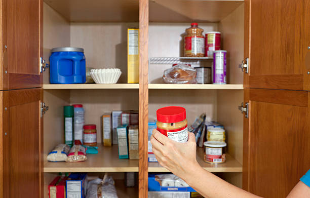 taking peanut butter out of the food pantry - inside pantry grocery cupboard bildbanksfoton och bilder