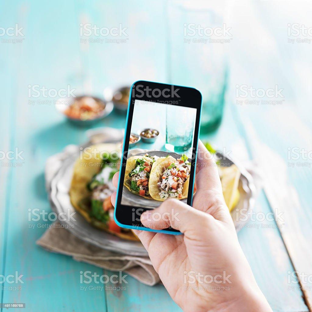 Nimmt Foto von carnitas street-tacos mit smart phone - Lizenzfrei 2015 Stock-Foto
