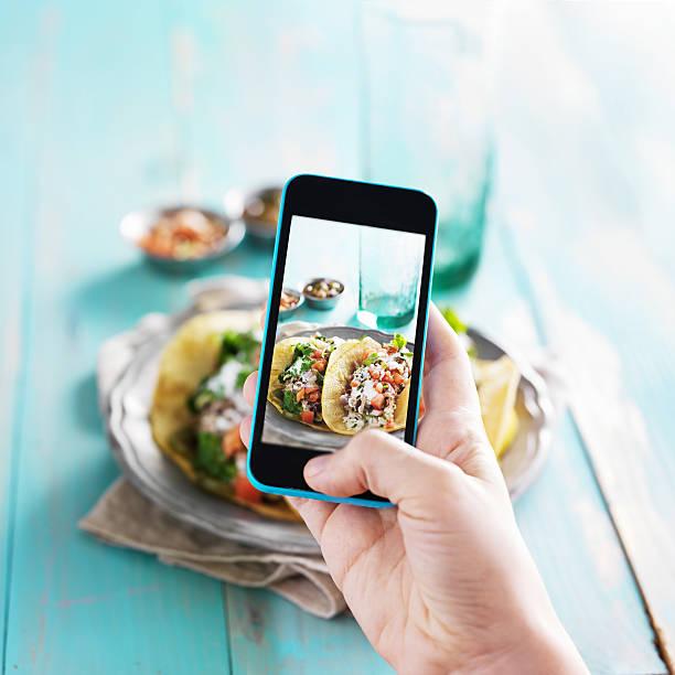 nimmt foto von carnitas street-tacos mit smart phone - fotohandy stock-fotos und bilder