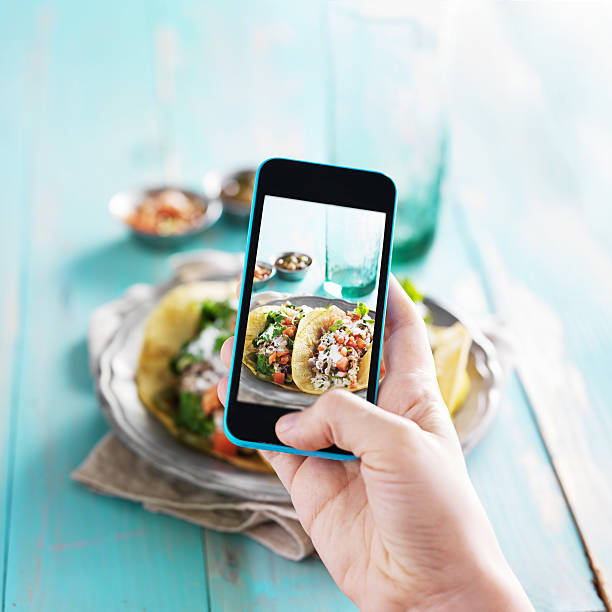 taking photo of carnitas street tacos with smart phone stock photo