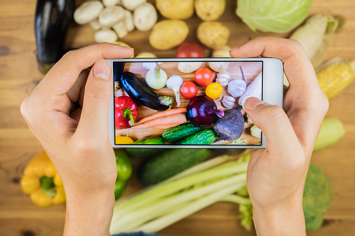 Taking photo of fresh organic vegetables on rustic wood table, top view