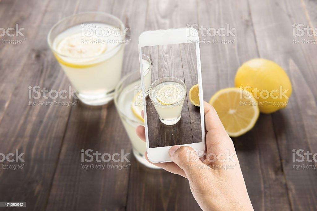 Taking photo of freshly squeezed lemon juice in glasses. stock photo
