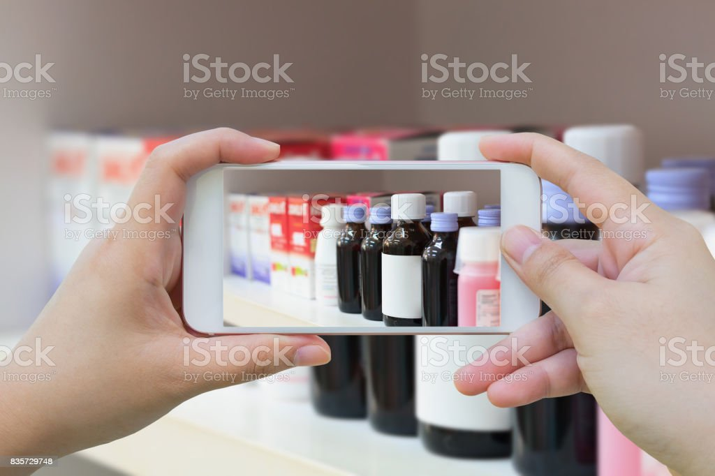 taking photo of medicine bottles in pharmacy store stock photo
