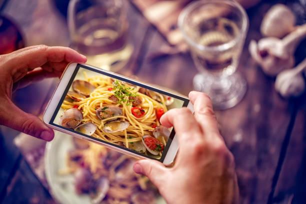 taking photo with smartphone of spaghetti alla vongole - pasta vongole bildbanksfoton och bilder