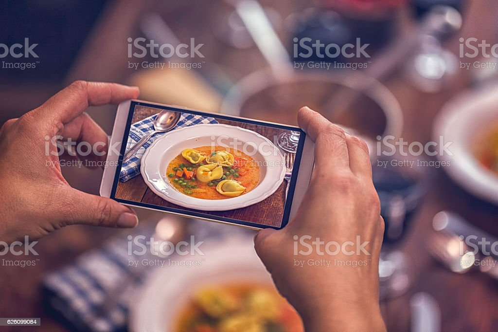 Taking Photo with Smartphone of Tortellini Soup stock photo