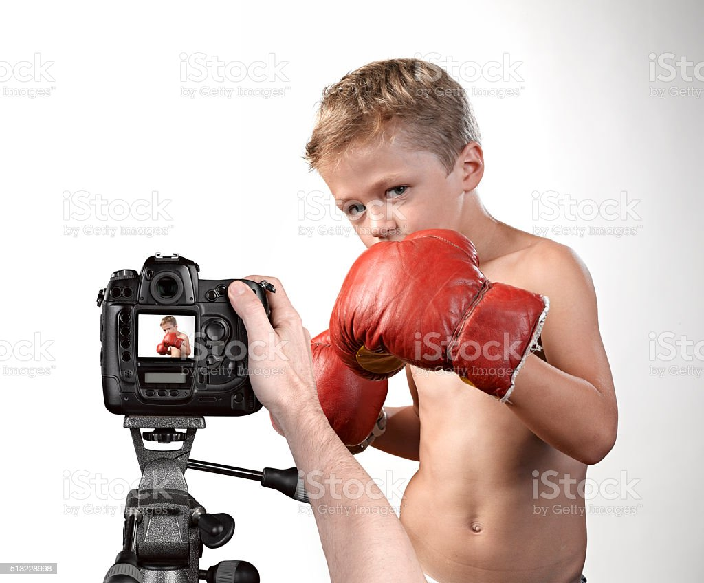 taking picture of a cute little boy with boxing gloves stock photo