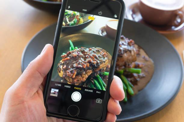 taking picture of beef steak with smartphone - instagram стоковые фото и изображения