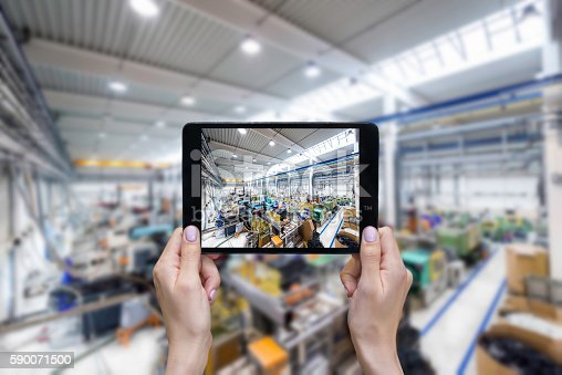 istock Taking picture of factory on a tablet 590071500