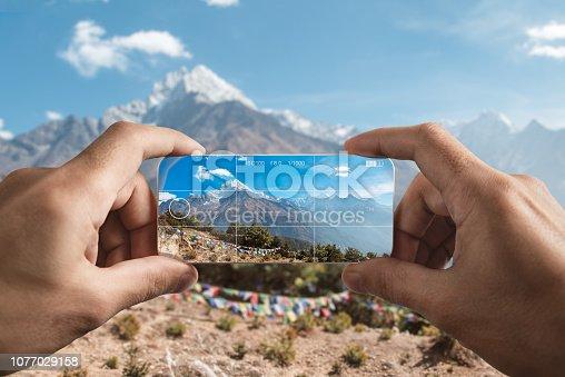 Taking picture using the mobile phone. Himalayan mountains: Kangtega, Tamserku, Kusum Kanguru, Kyashar. Sagarmatha National Park